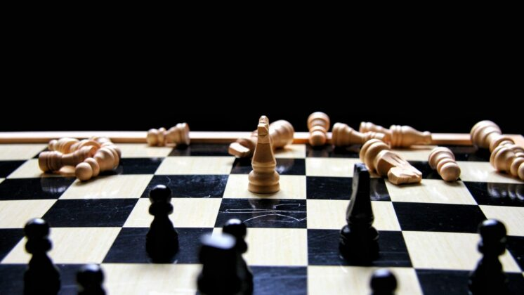 Black chess pieces advance on a single surviving white knight piece