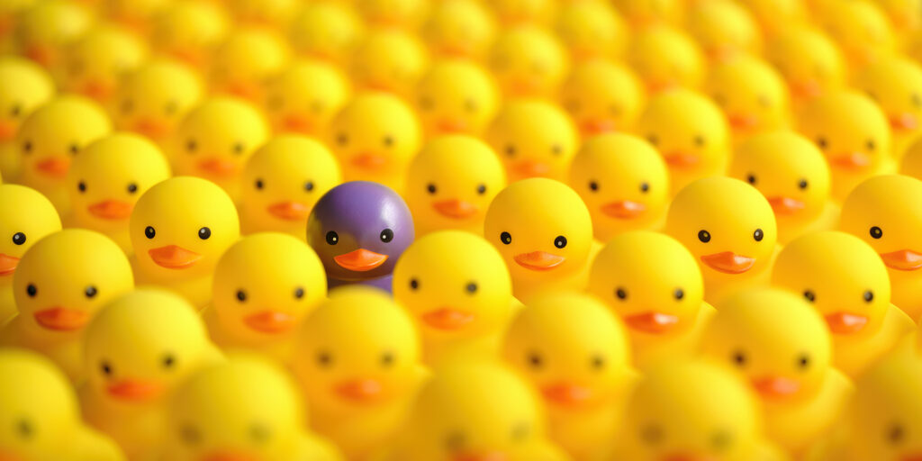 Large group of yellow rubber ducks, with one purple rubber duck showing how being different is important for brand presence