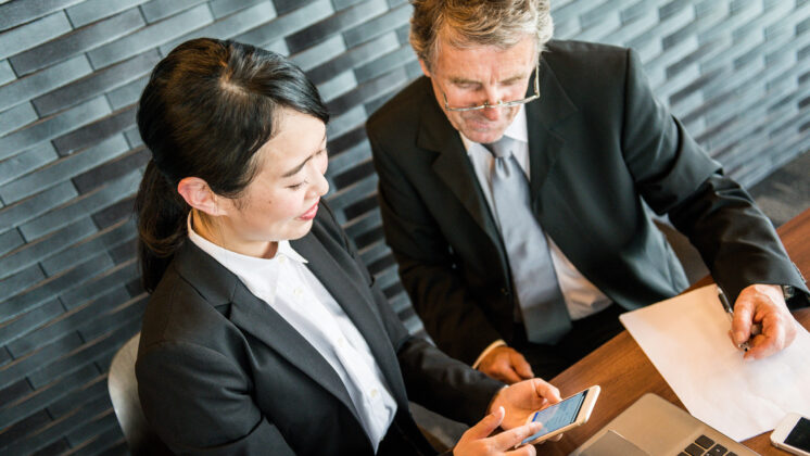 A Japanese woman and an American man discuss different business models on paper and mobile phone