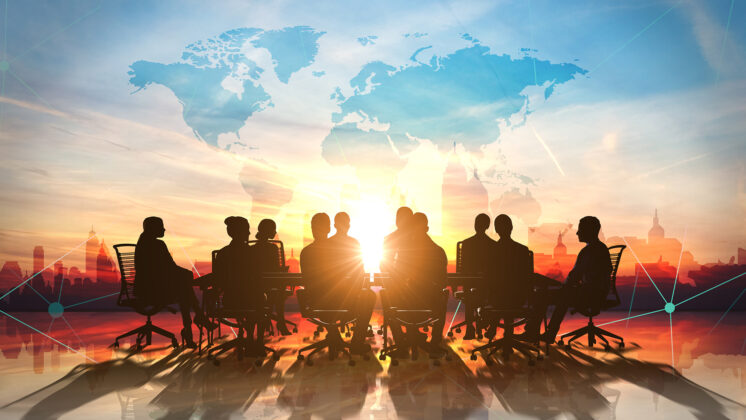 A table of global leaders with a bright sky in the background