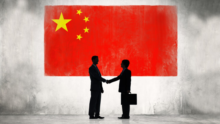 Silhouette of two men shaking hands with Chinese flag in the background