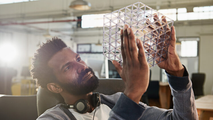 Young businessman holds up clear cube frame, thoughtfully, performing a start-up opportunity assessment