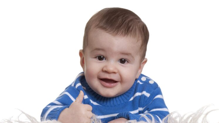 a baby in a blue sweater gives a thumbs up