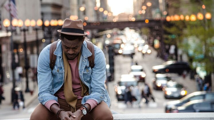 A traveling man sits on a bridge with his head down, suffering from the cultural stress of new situations