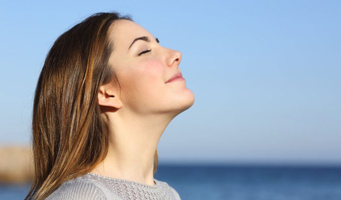 Woman at the seaside breathes in gently with a calm expression on her face