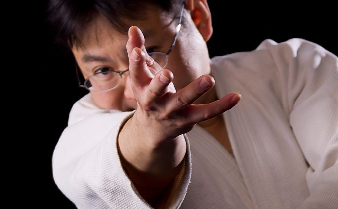 Tomoya Nakamura in aikido gear fiercely reaches for the camera in close up