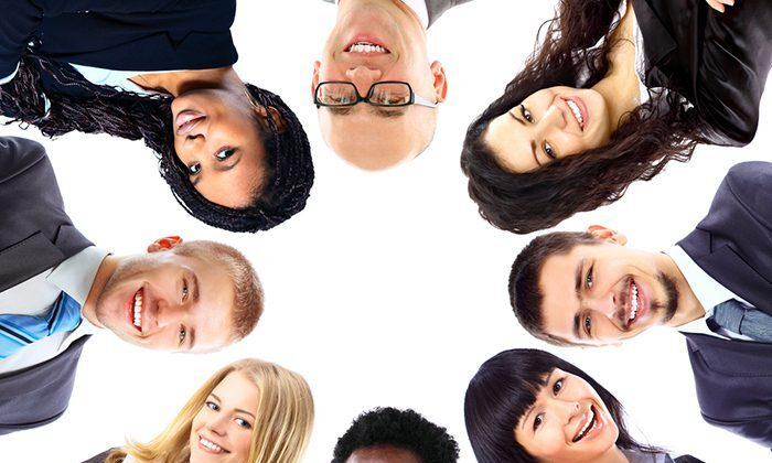 Eight young, diverse people in business attire assemble in a circle and look down on the camera with a white background above