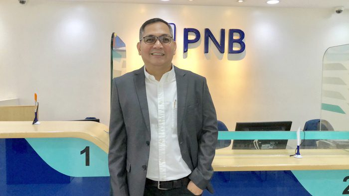 Roderick Enrique stands in a branch of the Philippine National Bank