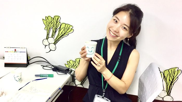 Christine Xuting holds up a cup with a smiling face on it