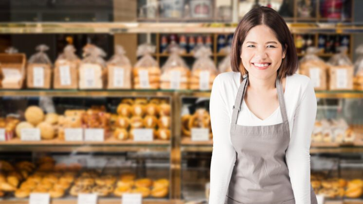 Entrepreneur woman stands smiling in front of a counter in a bakery
