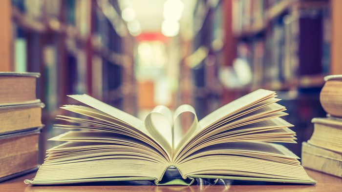 An open book with two pages folded in the shape of the heart.