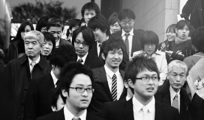 Black and white image of Japanese businessmen walking in a group