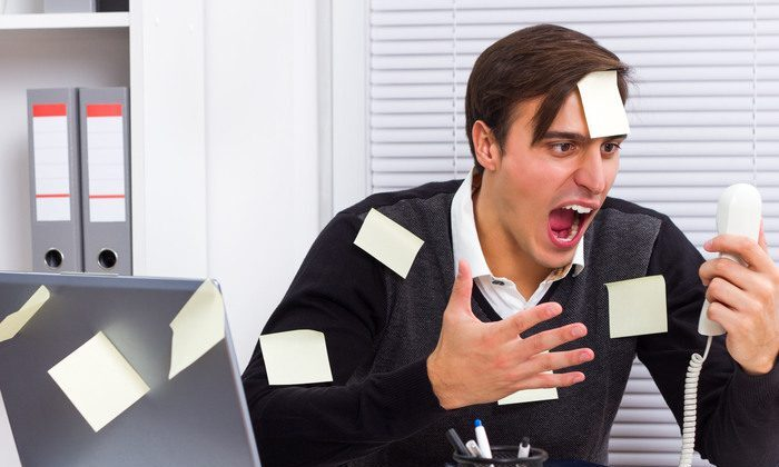 A man covered in post-its shouts at a phone at his desk, struggling with time management