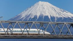 A Shinkansen races past Mt. Fuji, heading to a terminal where it will receive the famous