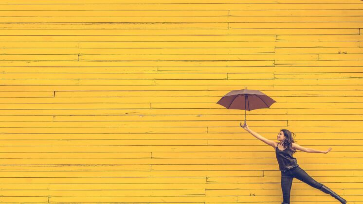 A woman holds an umbrella in front of a yellow wall.