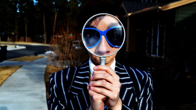 Man holding up a large magnifying glass to his face