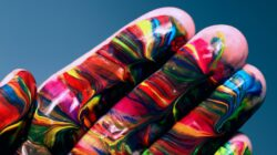 Image of a hand dipped in colorful swirls of paint, displaying both art and innovation