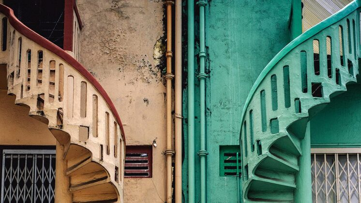 A beige spiral staircase is on the left. An identical green on is on the right.