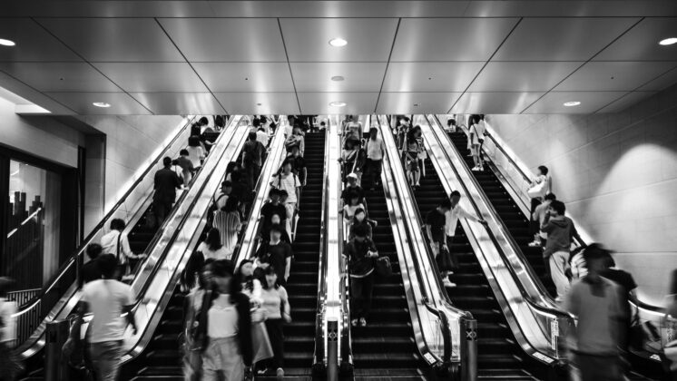 Black-and-white image of Japanese people riding escalators with strict etiquette to stand on the right side, observing a high-context culture
