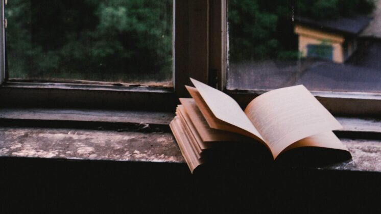 A book sits open on a aged windowsill.