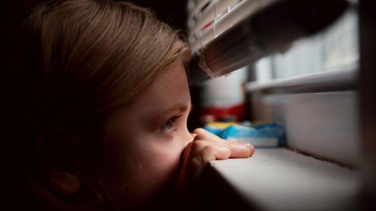 young girl stealthily peers out the bottom of a shaded window