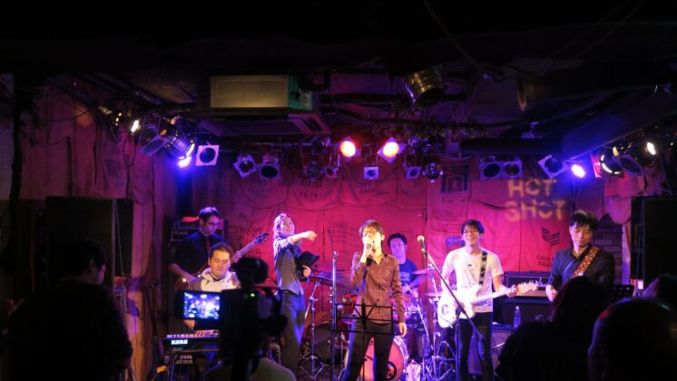 a seven member band plays under pink lights to an unseen crowd