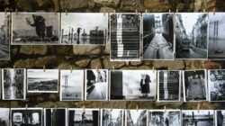 Both old and contemporary black and white photographs hang on a clothesline.