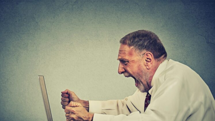 An older businessman screams at a laptop with fisted hands