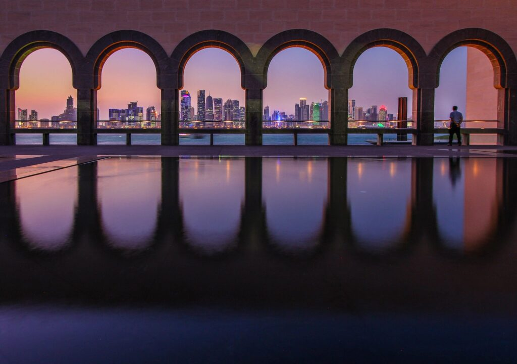 The Doha, Qatar skyline at twilight through museum arches