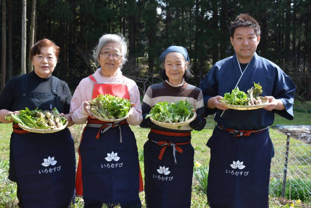 The staff of Iromusubi poses for the camera with trays of veggies in their hands.