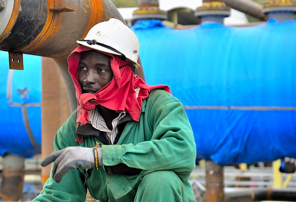 A Kenyan worker sits wearing a red scarf and a white hardhat.