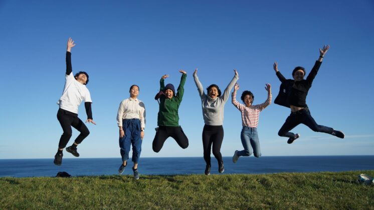 Six young people jump together on a grassy field with the ocean in the background