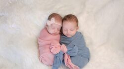 A boy baby and girl baby sleep in pink and blue swaddles tied together in a bow