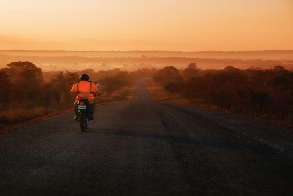 A lone biker in an orange jacket driving down the Great East Road of Zambia in the orange evening light