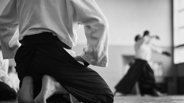 Black and white image of aikido student kneeling with blurred partners training in the background
