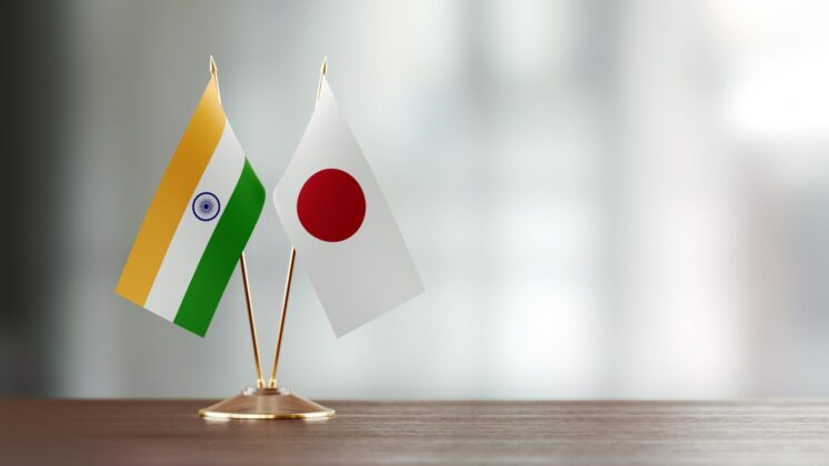 Japanese and Indian flags on a desk with an unfocused background