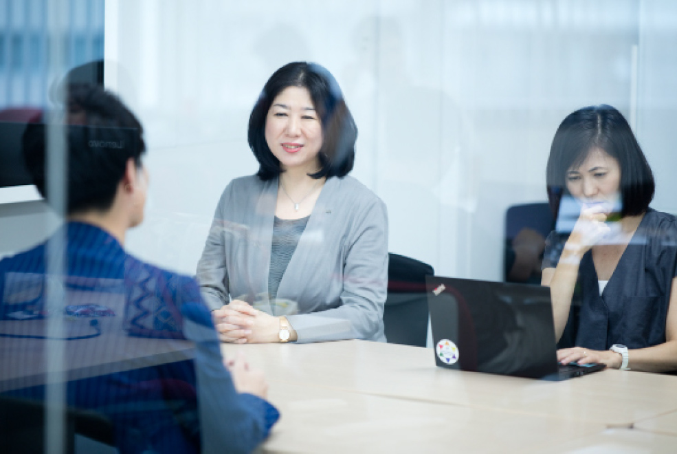 Ms. Obara and two others in a glass-walled meeting room at AXA Insurance