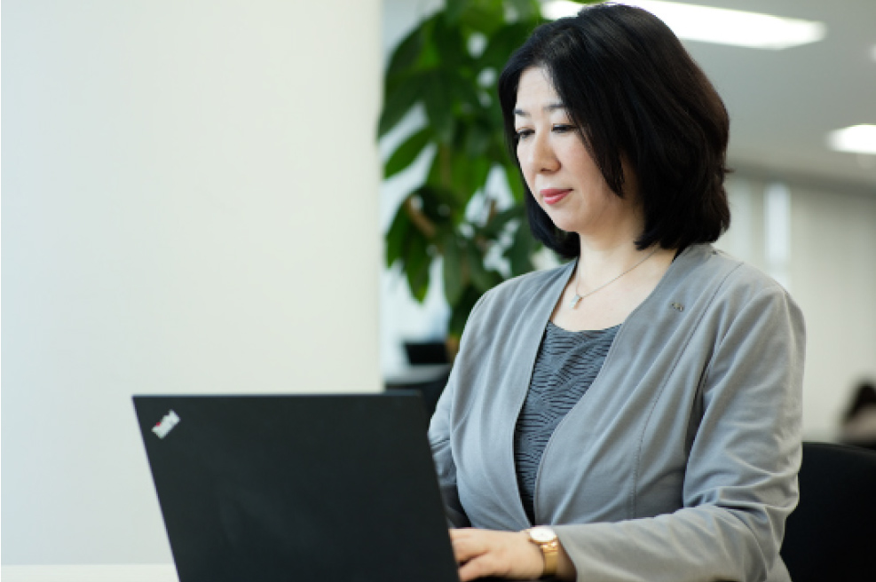 Ms. Nanae Obara working on her laptop at the AXA Insurance offices