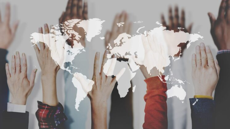 Hands of various ethnicities rise up behind a superimposed map of the world