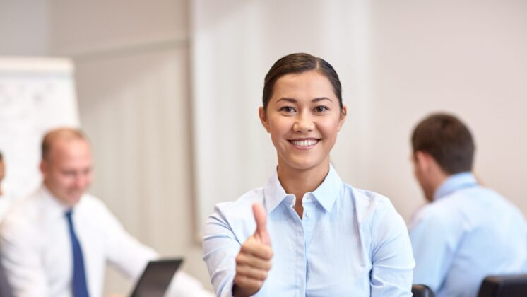 smiling businesswoman showing thumbs up with group of businesspeople meeting in office