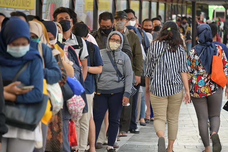 A large line of people wearing masks wait for a bus.