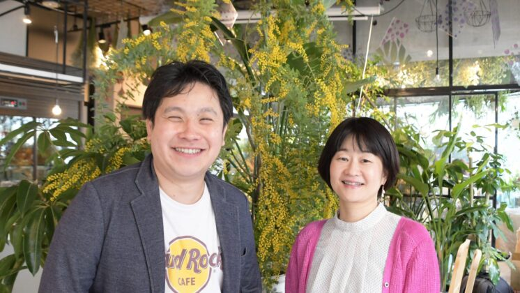 Mr. Narisawa and Ms. Namba smile for the camera in a large room filled with yellow flowering trees