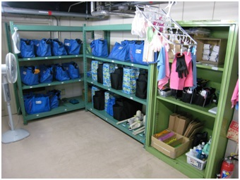 The back room of the Shinkansen cleaning staff, with cleaning supplies and duffel bags neatly arranged on shelves.