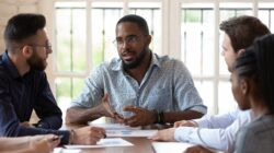 Concentrated Black male manager talks to diverse colleagues in the office.