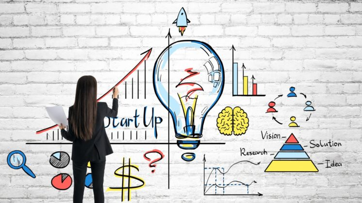 Businesswoman drawing creative business sketch with lamp on brick wall background. Idea and startup concept