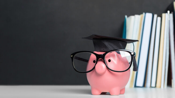 A pink piggy bank with glasses and a graduation hat beside a stack of books, representing how education and student loans go hand in hand