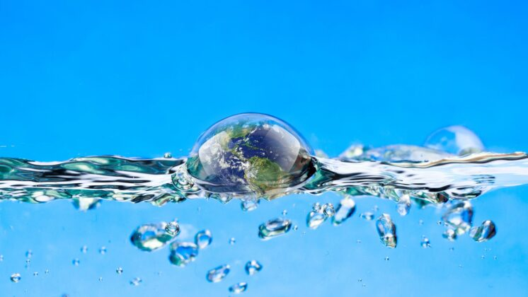 A blue background showing a cross-section of water with bubbles below the surface and a larger bubble reflecting the world just breaking the surface