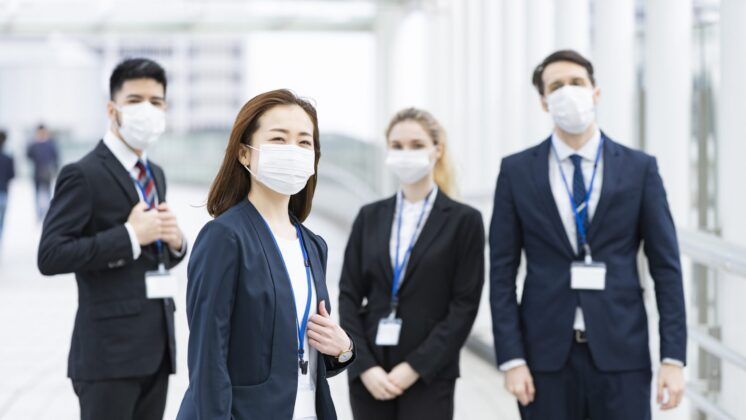 A group of international employees wearing masks gazes at the camera