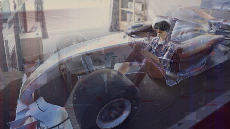 A man sits in his living room driving a virtual reality racing car