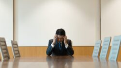 Businessman at an empty boardroom table holds his head in his hands in shame over bankruptcy